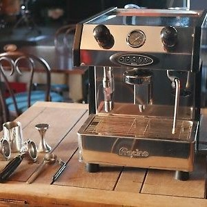 Fracino Bambino espresso machine with filter holders in cafe, front view, chrome