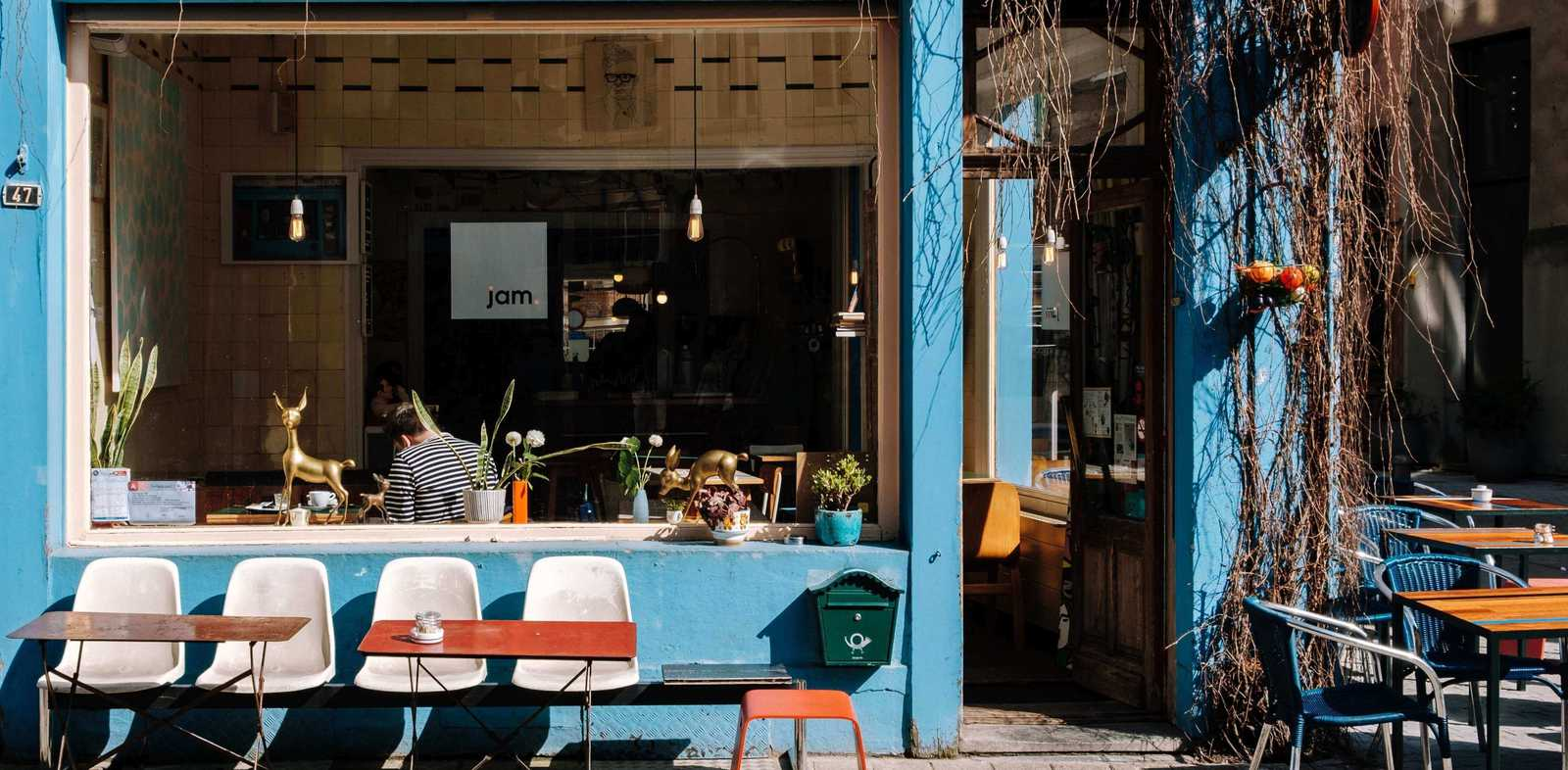 The outside of a cafe with chairs and tables - Blog image for top commercial bean to cup coffee machine of 2019 blog post